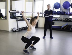 woman excercising with physiotherapist near by