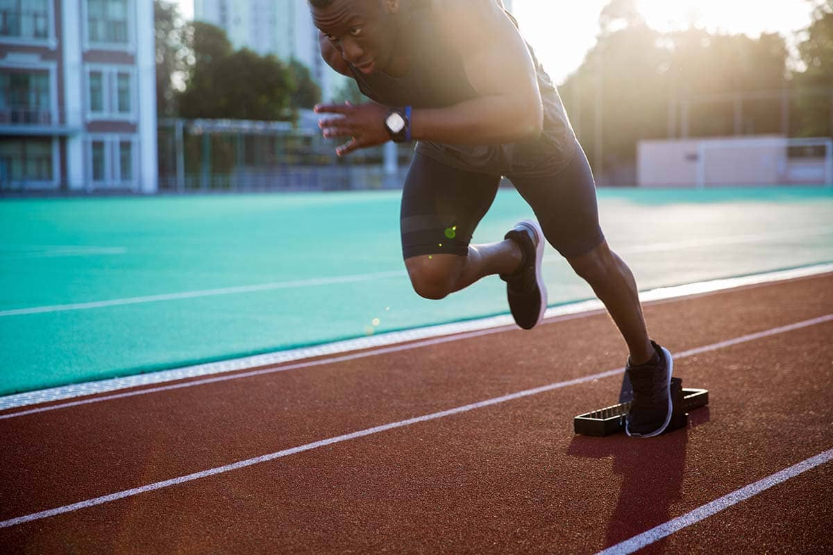 athlete running on track during athletic therapy