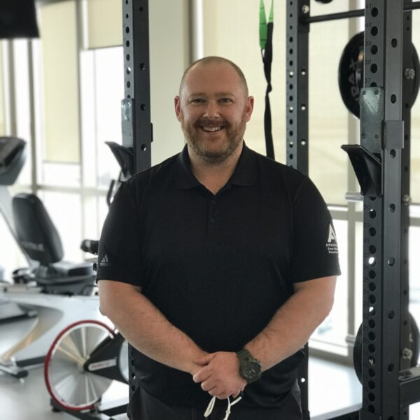 man wearing t shirt standing in front of workout equipment